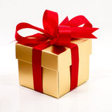 Beautiful gold present box with red bow and ribbons Stock Images
