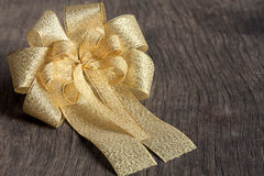 Beautiful gold ribbon on wood background. Royalty Free Stock Image
