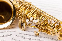 Beautiful golden alto saxophone on musical notes Stock Photo