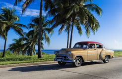 Beautiful golden american Oldtimer drives on the promenade in Havana Cuba - Serie Cuba 2016 Reportage Royalty Free Stock Photography