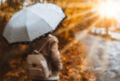 Beautiful golden autumn season. Watercolor like blurred blond girl with backpack and bright umbrella stands under rainy. Drops and droplets. Backlit sunset sun Stock Photos