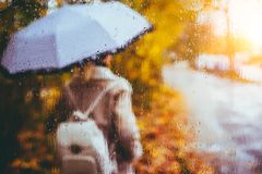 Beautiful golden autumn season. Watercolor like blurred blond girl with backpack and bright umbrella stands under rainy stock photo