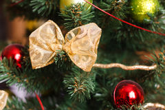Beautiful golden bow and red, green Christmas balls on artificia royalty free stock images