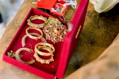 Beautiful golden bracelets and rings on bed. Wedding gold bangles and bracelets. royalty free stock photography