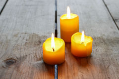Beautiful golden candles on wooden table Royalty Free Stock Photo