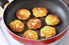 Beautiful golden cheese pancakes fried in a pan. Royalty Free Stock Images