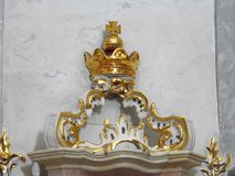 Golden crown in old church, Lithuania. Beautiful golden crown and white wall in old church in Liskiava town stock image