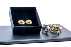 Beautiful golden earrings in a box and two watches Royalty Free Stock Photos