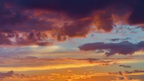 Beautiful golden fiery sunset, vibrant purple clouds, evening sky. Natural background, art shades Stock Image