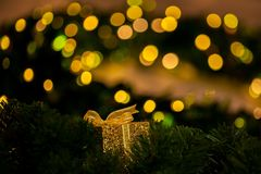 Beautiful golden gift decorated on Christmas tree blurred in gold bokeh background - selective focus. Royalty Free Stock Photo