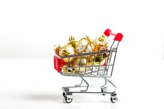 Beautiful golden gifts with ribbon and Christmas balls in shopping cart Stock Photos