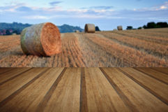 Beautiful golden hour hay bales sunset landscape with wooden pla Stock Photo