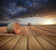 Beautiful golden hour hay bales sunset landscape with wooden pla Royalty Free Stock Photo