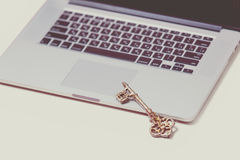 Beautiful golden key and cool silver laptop on the wonderful pin Royalty Free Stock Image