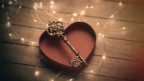 Beautiful golden key in opened heart shaped box and garland on t. He wonderful brown background Royalty Free Stock Photo
