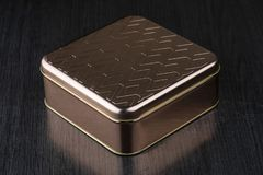 Beautiful golden metal box on a dark table isolated. Gift box stock photo