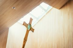 Golden metal crucifix in the church, incidence of light in the blurry background. Beautiful golden metal crucifix in church, incidence of light in the background stock photos