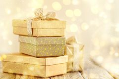 Beautiful golden presents for Christmas. Arrangement of shiny bright boxes decorated with ribbons in glowing lights stock image