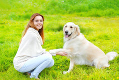 Beautiful Golden Retriever dog gives paw owner on the grass Royalty Free Stock Image