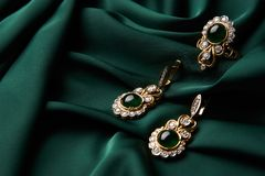 Golden ring and pair of earrings with green Emerald and Diamonds royalty free stock images