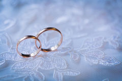 Beautiful golden rings on the blue wedding dress Stock Image