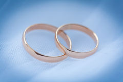 Beautiful golden rings on the blue wedding dress Stock Photos