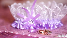 Beautiful golden rings and garter on the table.  stock footage