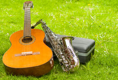 Beautiful golden saxophone and acoustic guitar lying across black instumental case on grassy surface Royalty Free Stock Photography