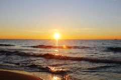 Beautiful golden sunset on the beach. With waves and sailing ship in the background. Thank you for your DOWNLOAD Stock Photos
