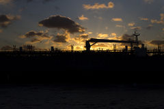 Beautiful golden sunset behind a silhouette of a big cargo ship Stock Photography