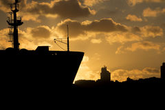Beautiful golden sunset behind a silhouette of a big cargo ship Royalty Free Stock Photo