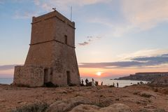 Golden sunset at Ghajn Tuffieha Tower. Beautiful golden sunset at Ghajn Tuffieha Tower, above Golden Bay, ancient watchtower built by the Knights of St. John Royalty Free Stock Photography