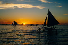 Beautiful golden sunset over fishing boats and people in water Royalty Free Stock Photography