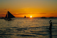 Beautiful golden sunset over fishing boats and people in water Stock Images
