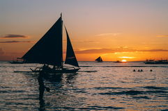Beautiful golden sunset over fishing boats and people in water Royalty Free Stock Image