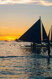 Beautiful golden sunset over fishing boats and people in water Stock Photography