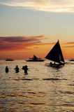 Beautiful golden sunset over fishing boats and people in water.  Royalty Free Stock Image