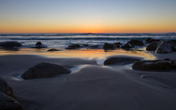 Beautiful Golden Sunset over Rocky Beach. Golden sunset reflecting on the sea on an isolated rocky beach Stock Photo