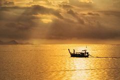 A beautiful golden sunset on the sea. A beautiful golden sunset on the sea,Asian fisherman on wooden boat with sunset time Royalty Free Stock Images