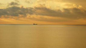 Beautiful golden surface of the sea and ship on the horizon and clouds in the evening Stock Photo