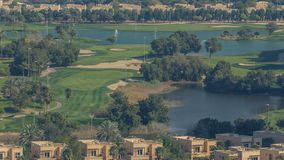 Beautiful golf course near modern skyscrapers of Dubai Marina timelapse in luxury Dubai city, United Arab Emirates. Fountain, lakes and golf cars moves on lawn stock video