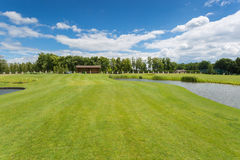 Beautiful golf course with perfect grass and water hindrance at. Beautiful golf course with perfect green grass and water hindrance at bright sunny day royalty free stock photos