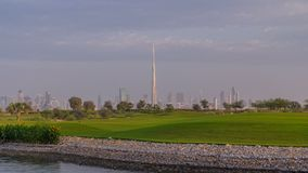 Beautiful golf course during sunrise around modern skyscrapers of Dubai Downtown timelapse in luxury Dubai city, United. Arab Emirates. Green lawn, pond and stock footage