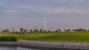 Beautiful golf course during sunrise around modern skyscrapers of Dubai Downtown timelapse in luxury Dubai city, United. Arab Emirates. Green lawn, pond and stock video