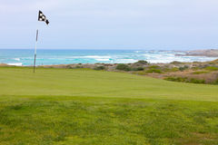 Beautiful golf hole green with flag on California ocean coast. Beautiful, manicured golf course hole. The green, smooth grass and flag overlook the rugged Royalty Free Stock Photos