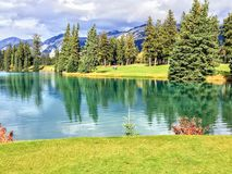A beautiful golf hole in the Jasper, Alberta, high in the Rockies mountains.  The fairway is beside a beautiful lake. That reflects the surrounding forest in royalty free stock image