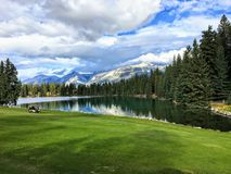 A beautiful golf hole in the Jasper, Alberta, high in the Rockies mountains.  The fairway is beside a beautiful lake. That reflects the surrounding forest in royalty free stock photo