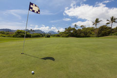Beautiful golf hole on tropical island. Golf flag indicating the hole on a scenic, smooth green golf green on a beautiful golf course on a tropical island. Hills Stock Image