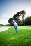 Beautiful golfing scenery with a golfer holding a club. Beautiful scenery with a golfer, course, sunset landscape Royalty Free Stock Images