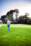 Beautiful golfing scenery with a golfer holding a club. Beautiful scenery with a golfer, course, sunset landscape Stock Image